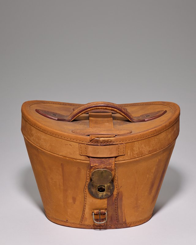 light tan leather case with concave top; metal buckles; hinged lid with handle on top of case; green silk lining with gathered fabric on inner lid