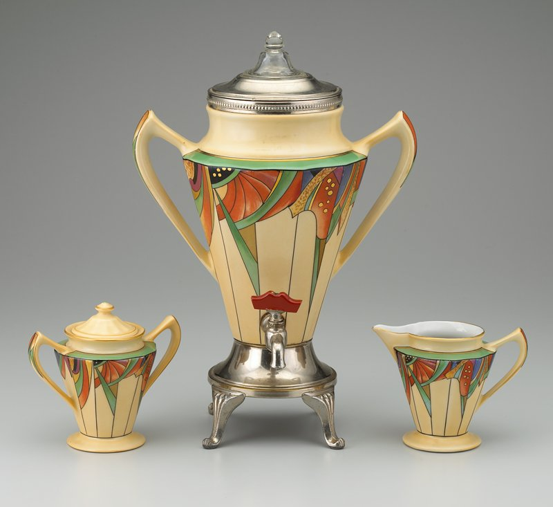 ceramic urn-shaped with pair of handles; cream underglaze with green, black, orange, blue, purple, brown and gilt Deco design at shoulder and handles; percolator insert; metal lid with glass knob; 4-footed metal base and metal spigot