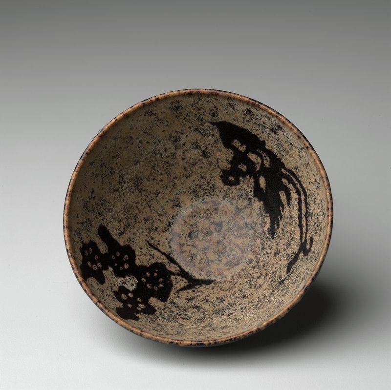 small, deep bowl; dark brown glaze on exterior; mottled tan and brown glaze on interior with stenciled designs in dark and brown of bird and flower
