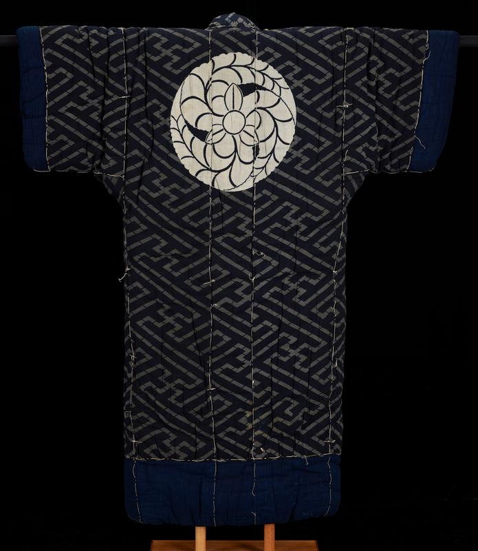 thick, padded kimono; grey and black geometric design on torso and sleeves; grey and black multi-directional diagonal stripe pattern with grey clockwise swastikas connecting grey lines; indigo lining throughout interior; indigo bands around sleeve ends and bottom; indigo rectangles at bottom of front opening flaps; large off-white circular design of flower and spiraling leaves on upper back; katazome technique