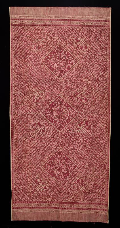 hand-drawn batik; purplish-red and off-white panel; red and off-white striped band at each short end; off-white and red bands form borders with four-dot motif in some bands; three large diamonds in a row in center with four-petal flowers inside diamonds; eight looped line motifs by diamonds; looping line designs radiating out from diamond edges: single loop, half-spiral and curvy W-shaped designs with dot clusters throughout