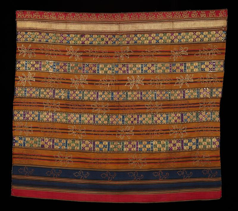 red, yellow, dark blue and black with some brown, off-white and green; couched gold thread; light blue, green, purple, gold and red embroidery; two panels, sewn together; red, blue and yellow bands with black, green, brown, off-white and red thin bands between larger bands; gold embroidery in squiggly-lined contour shapes; bands of gold squares with purple, blue and green X and diamond shapes between them, with gold sequins inside design and bordering bands; along one long edge thick gold thread and sequins in scallop and pointed shape pattern; second band from one long edge is gold thread with red thread diamond pattern; small folded and stitched hem along short edges