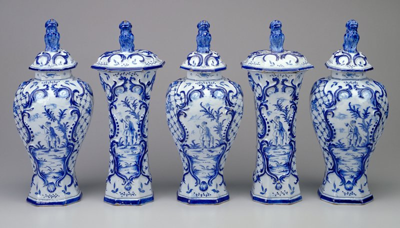 conical shape vase with slightly flaring mouth and foot; octagonal mouth opening; wide, slightly domed lid surmounted by dog; woodcutter next to tree on front and back inside a Rococo cartouche; flowers and lattice throughout; blue and white