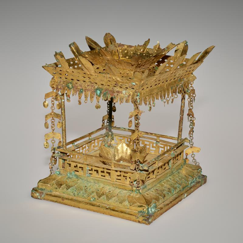 "small square pavilion with lotus flower at center; openwork ""railing"" with L-shaped openings; pedals around outer edge of base; canopy edged in triangular pattern with round hanging pendants at bottom of each; chains with chevron and round pendants at corners; petals around top edge and central element on canopy; shipped with dark colored wooden base"