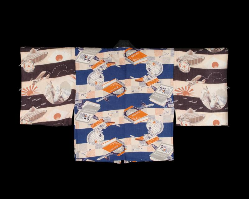 half-length shirt with whimsical patterns; blue striped body, with repeating pattern of boxes of crayons, globes, and sheet music with Mickey Mouse on it; sleeves are patterned with wide black stripes, and repeating pattern of horses, flags and tanks