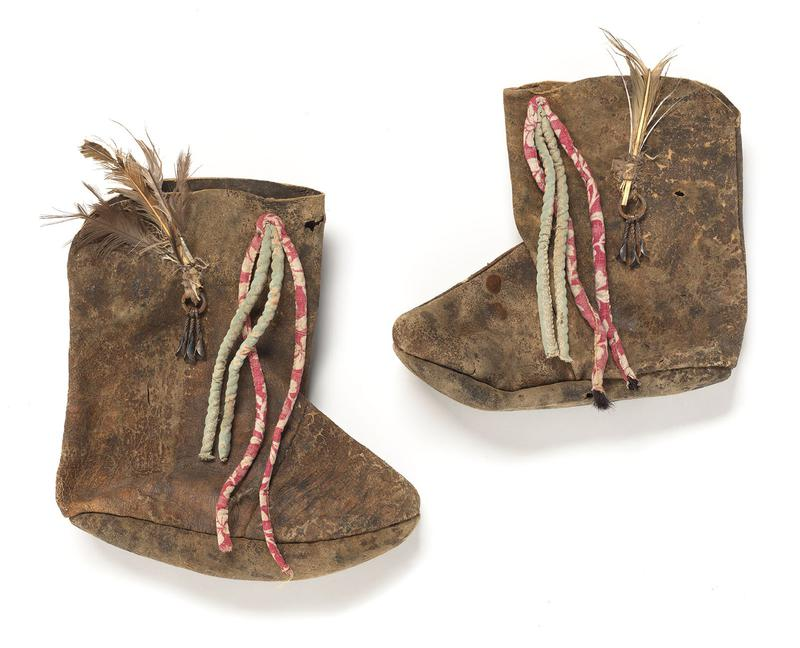 pair of tan boots, with cloth decorative cords in pale green and red and white printed fabric; metal rings at outer center of each boot, with metal decorative cones, and tan feathers extending upwards
