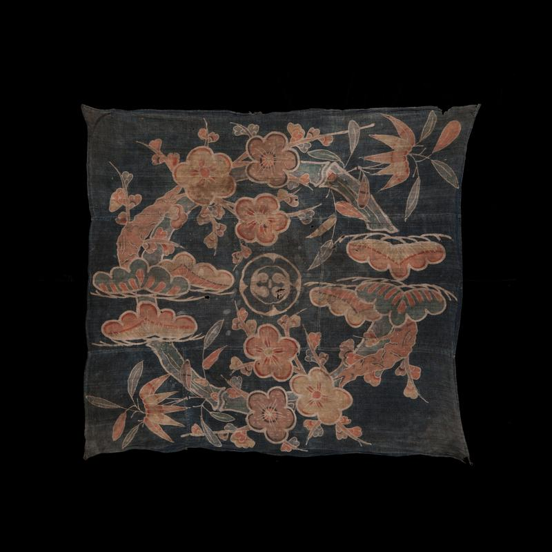 faded blue cloth with circular design in stylized floral elements in faded oranges, browns, peach and blues; crest in blue and white swirling designs in center