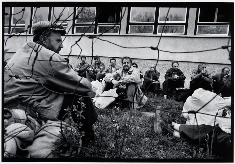 men seated on grass behind fence, central man elbows on knees and hands together in front