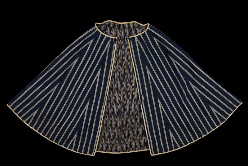 navy blue cape with tan vertical stripes and triangles on outer side; navy blue, brown, and tan patterned lining; two brown hooks attached by navy rope at neck; two rope loops at shoulders/back of neck (one navy, one black); navy rope loops at PR hip and PL front center; beige border with line of openings