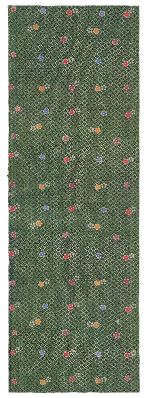 rectangular fragment of green fabric with black and white patterns in background, and red, orange, blue, purple, and white flowers overtop