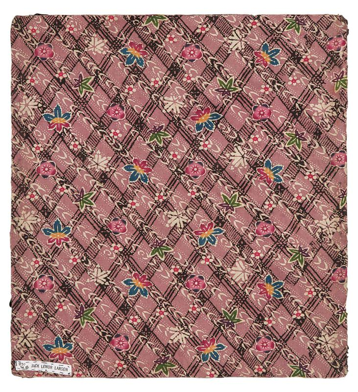 rectangular fragment of pink fabric with black diamond lattice patter in background, with diagonal, white leaf pattern over top and multicolored leave and blossoms throughout (green and purple leaves; blue, yellow, and red leaves; pink, purple, and red blossoms)
