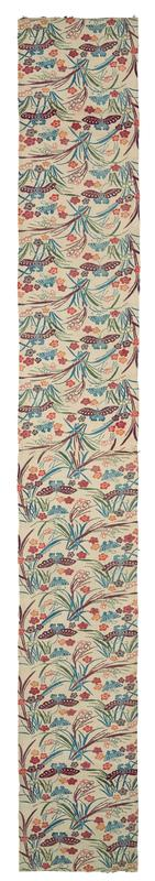 long, rectangular piece of fabric with blue, purple, green, red, and orange pattern on white background; green, blue, and purple grasses; red, orange, and purple flowers; blue and purple butterflies; pattern changes direction at center