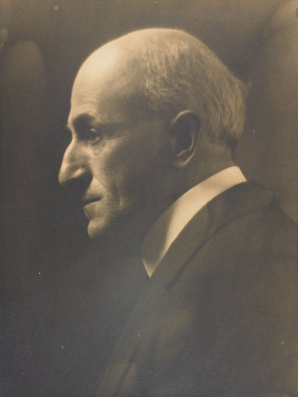PL profile of balding man with white hair; wearing dark suit and shirt with white collar