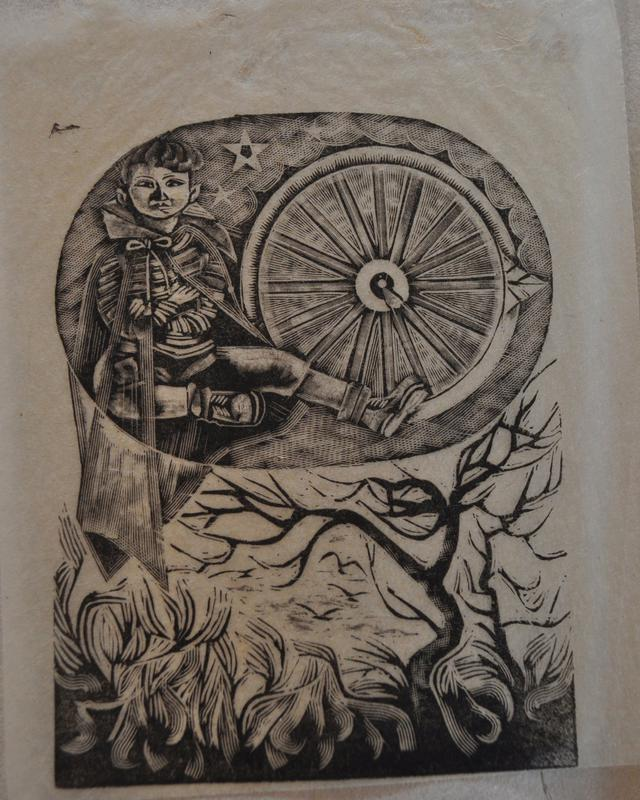 oval shape with image inside- wheel on left, seated child wearing a transparent cloak on right; two stars to the left of child's head; scattered trees and thickets at bottom of image