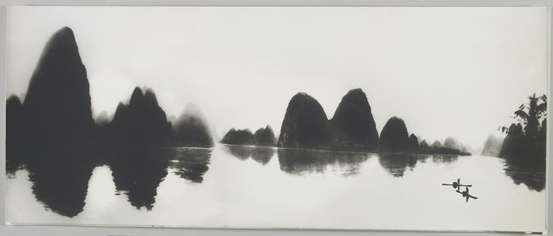 2 figures wearing hats and standing on boats at LRC; dark land forms reflected in the water, with trees at R; Li River, Peoples Republic of China