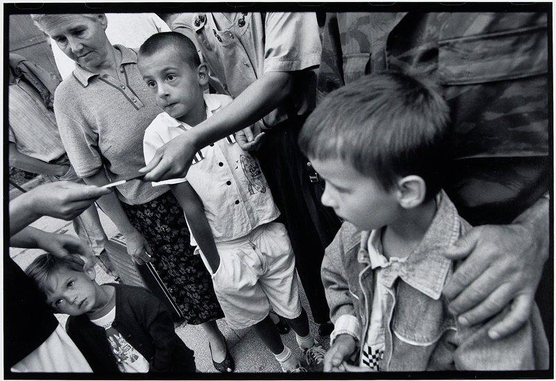 three children watching a woman hand a passport to someone off camera