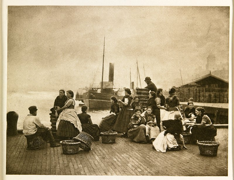 group of women and 2 men seated on a dock with scattered baskets; foggy water behind with one boat; from a portfolio with essay on the photographer