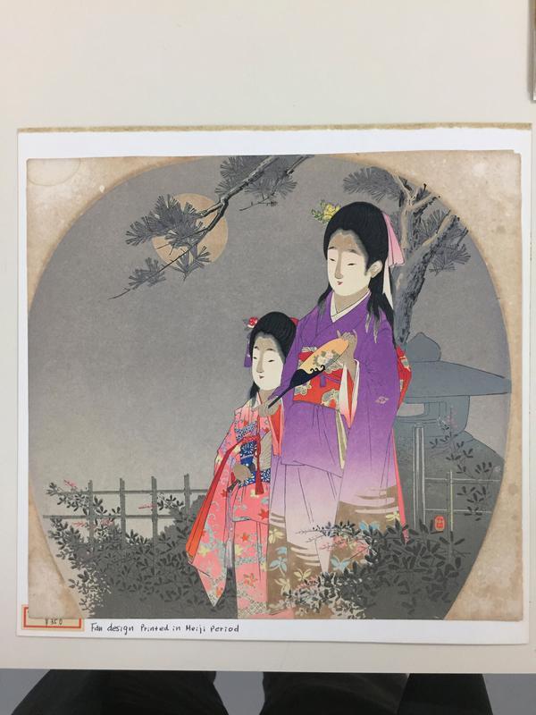 two young girls--one wearing pink kimono, one wearing purple kimono--outdoors at night