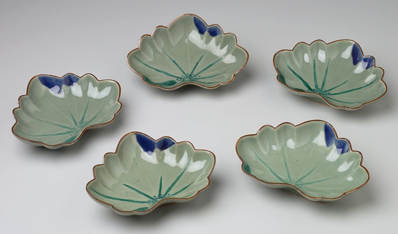leaf shaped dish; pale green with brown rim; inside of dish dark green starburst bottom center; curved dark green shape left of starburst; curved dark blue shape above starburst