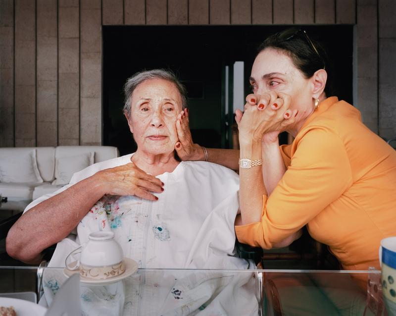 two woman in an interior seated at a glass table; elderly woman wearing white holds her hand to her chest and a younger woman wearing orange seated to the older woman's left holds her other hand to her face