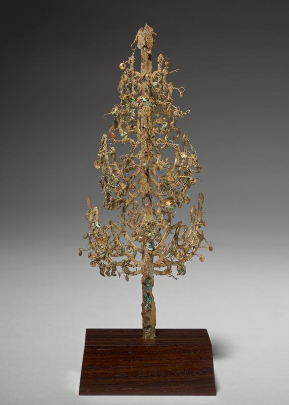 angled piece of gilt bronze, tapering at top, with decorative cutout pattern creating branches/body of tree; twisted wire loops attached to branches and body of tree, with small circular disks hanging from loops; trunk piece has reinforcement piece attached to backside