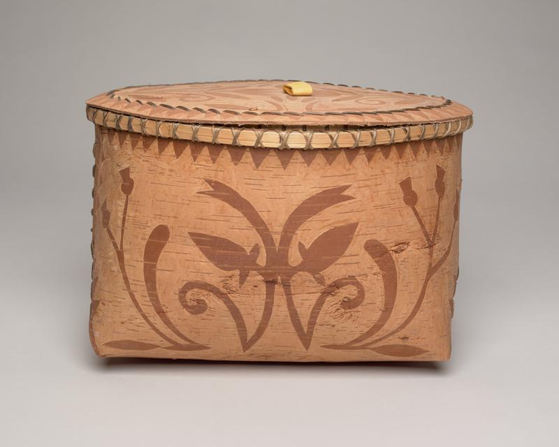 birchbark folded basket with lid; rectangular base, diamond shaped opening, diamond shaped lid; light brown with darker brown designs: matching floral pattern on front and back, diamond with rays on either side; panels secured on either side with straight stitches; overlapping stitches over rim; white, raw birch bark interior; flat lid with tan leather pull looped through center, tied to stretcher bar on underside; lid top decorated with tulip floral design with triangular pattern around edge and straps attaching bottom lip worked into triangular pattern; underside of lid raw, white and gray bark