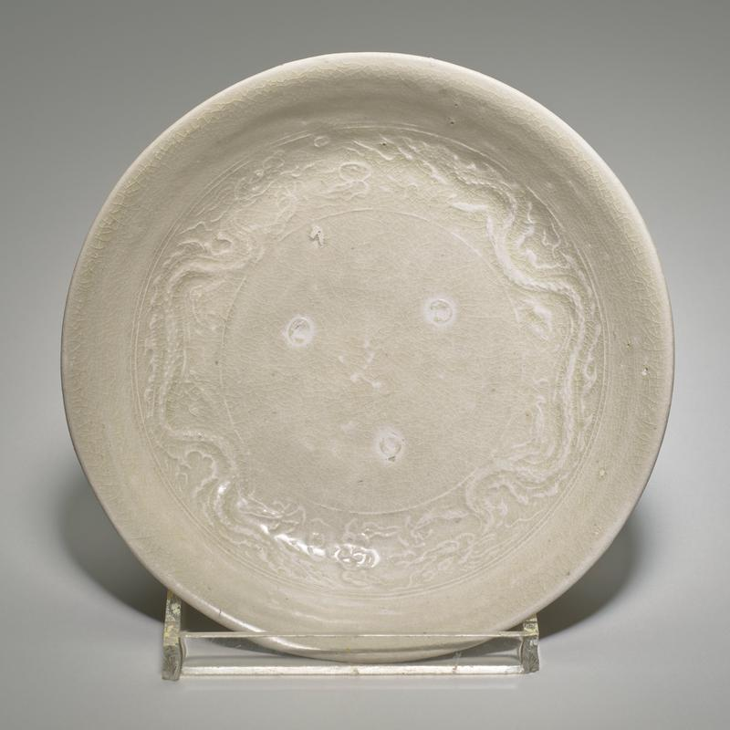 shallow dish with short foot; light grayish glaze; pair of lightly molded dragons around bottom of rim on interior