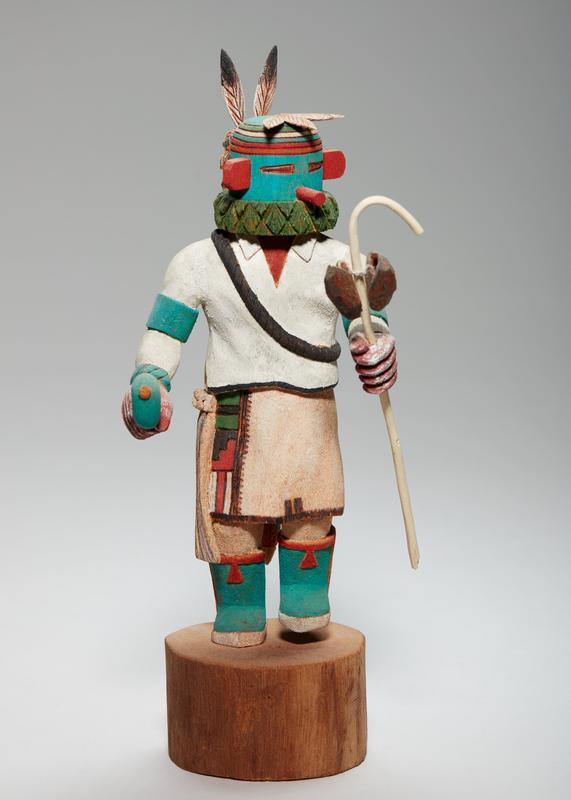 carved, painted figure, leaning slightly forward with PL foot slightly raised and an object in each hand (flat, round green object on stick in PR hand; longer stick with 2 brown/red attachments tied on in PL); green face with brown slit eyes, a red post nose, and two red ears sticking out; three feathers lie on top of head, and two stick up in back from a small headpiece on back; green, white, and red stripes circle top of head; green neck piece; green arm bands and bracelets; brown sash over collared white shirt; tan skirt with brown, red and green pattern on PR side, gray animal with red eyes on backside, and long, tan and brown attachment on PL side; green boots with red trim; figure standing on wood round with knot/branch stub on back side