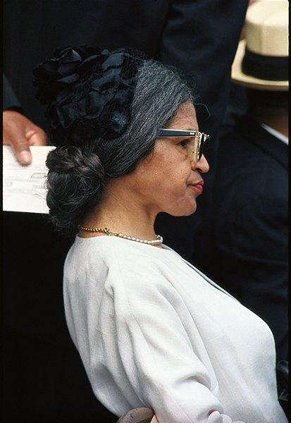 color image of a middle-aged woman in profile from PR, with dark hair streaked with grey pulled into a low bun, wearing glasses, a small black hat, pearl necklace and white jacket; received in black frame