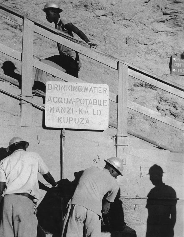 """Black and white photograph of man ascending a staircase while two others wash their hands below a sign that reads """"Drinking water"""" in several languages"""