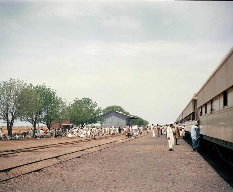 Color photograph of a train station; people wear mostly white and wait along L side of image; a yellow train along R side