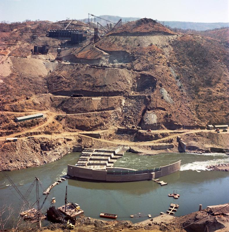 Color photograph of a mined hillside with a river at it's foot