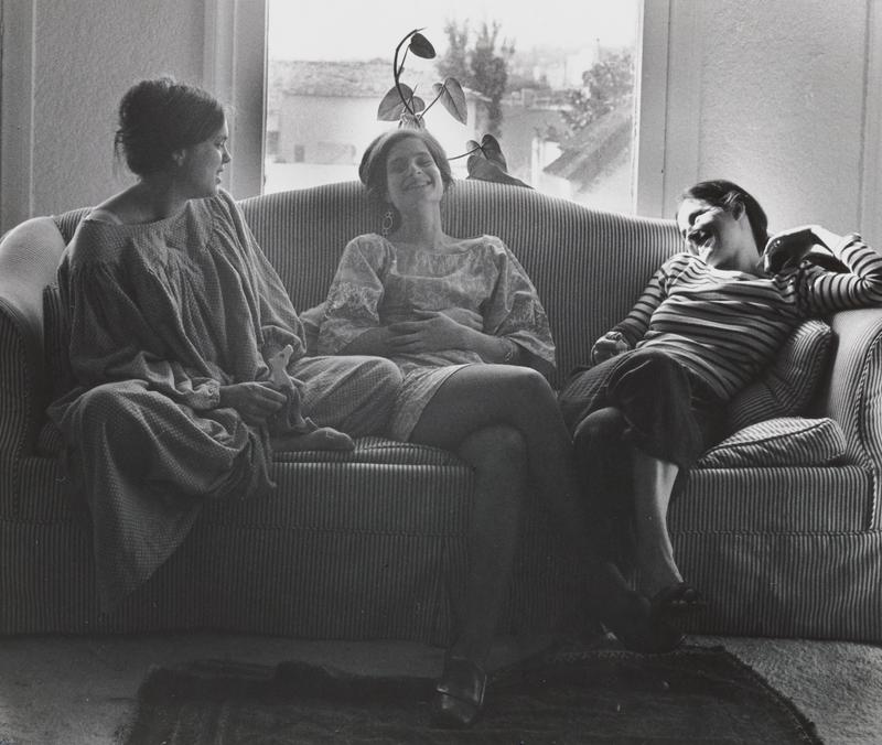 black and white image of three young women seated on a striped couch with a plant in front of a window in background; woman at center has her hands on her stomach