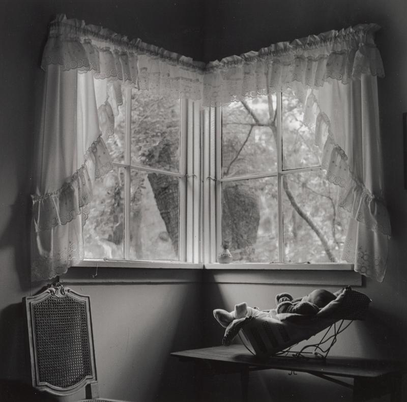 black and white image of a baby in a reclining bouncy seat on a table beneath two windows with eyelet-trimmed curtains in a corner