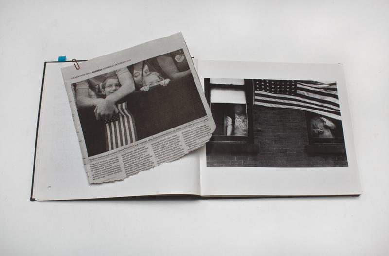 newspaper clipping with a photograph of two children peeking over the top of a black barrier with the arms of a man around the taller child, holding a U.S. flag, on top of a book with a photograph of two women looking out of windows, with their faces hidden, and a U.S. flag at top of image partially covering window at right