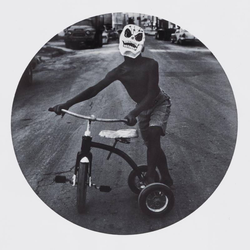 round black and white image of a little boy wearing a skeleton mask with a tricycle