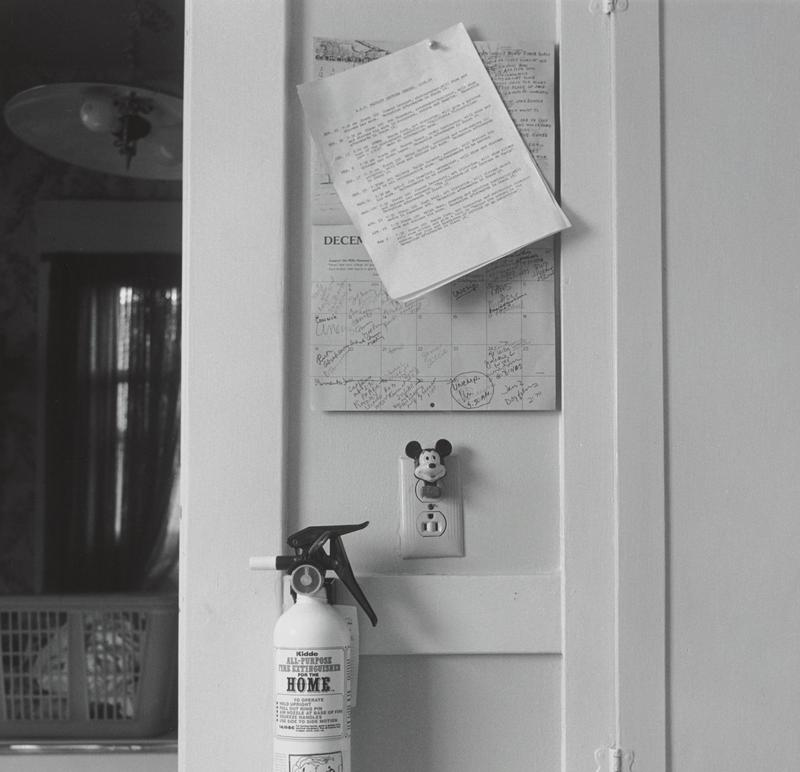 black and white image of a wall calendar with many notes and a typewritten page tacked over top of calendar; Mickey Mouse night light in outlet below calendar; fire extinguisher below outlet