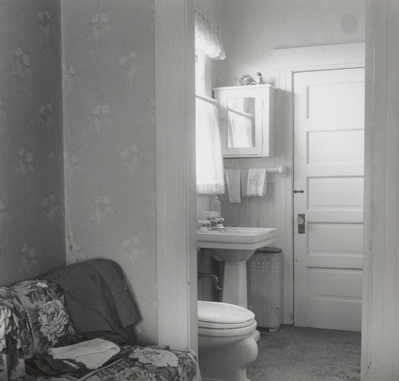 black and white image with a view into a bathroom with toilet and sink on left side of room seen through doorway, with a closed door with a glass doorknob beyond; floral couch with a jacket and towel at left; flowered wallpaper behind floral couch