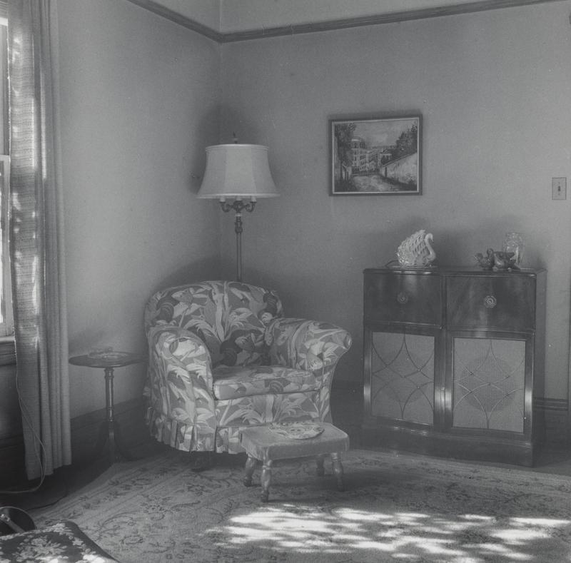 black and white image of a living room with a floral chair with a tall lamp behind it in corner, a footstool with turned wood legs and a console with a glass swan figure on top of it