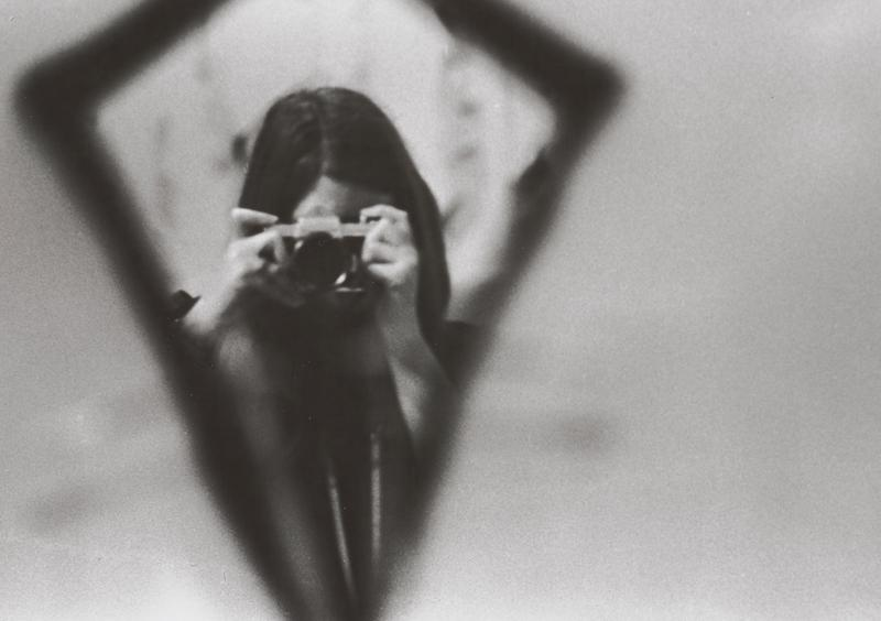 black and white image of a woman with dark hair holding a camera up in front of her face inside a diamond-shaped vignette