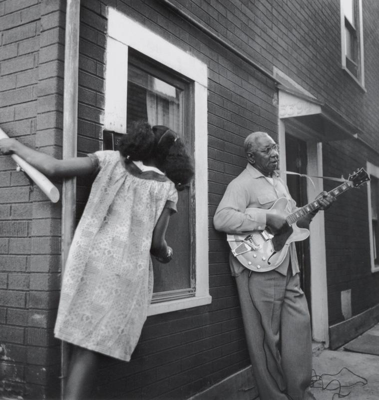 black and white image of a standing man playing an electric guitar, leaning against the outside of a brick building; girl at left seen from back, with her hair in two ponytails