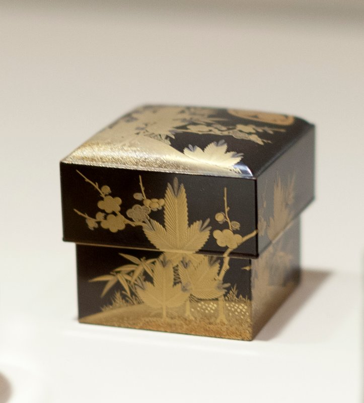 Square Toilet box of black lacquer decorated in gold and copper in tree and flower motives; bearing Crest of Tokugawa family, three asarum (ginger) leaves, their points together within a circle which appears twice on cover of box and one on box.