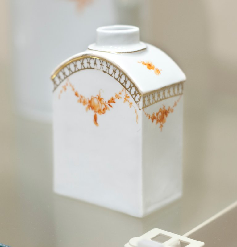 Tea Caddy, ceramic, rectangular gold band, floral swags in orange, German XVIIIc cat. card dims 4-3/4 x 2-1/2 x 1-1/2' ; Holiday Traditions, Northumberland Room