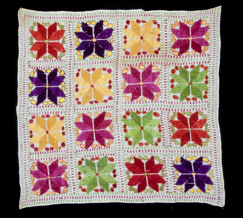 Square cushion cover embroidered in star design of many colors, on natural colored linen.