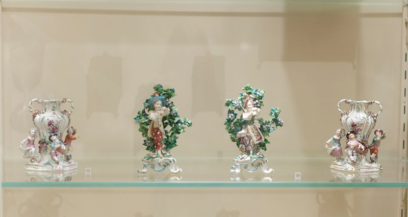 vase, ceramic-porcelain, one of a pair of old Chelsea vases comprising of three figures of children in dancing attitudes and playing musical instruments around a vase ornamented, delicately painted flowers and encrusted with colored flowers