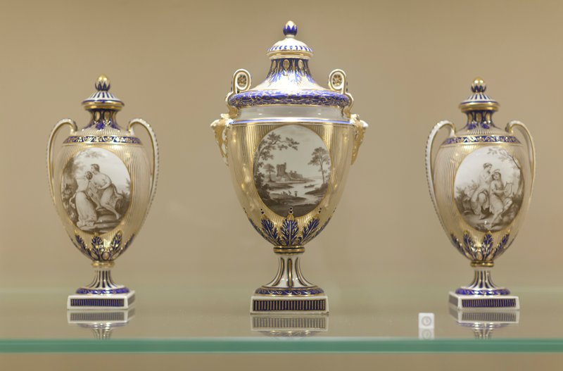 garniture of vases, oval panels in sepia of landscapes or figures, framed by striped gold background