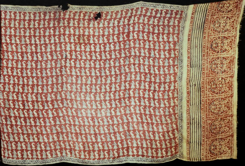 Turban Cloth; red ground with wood block and batik design in yellow of man holding bird alternating with leaf design.