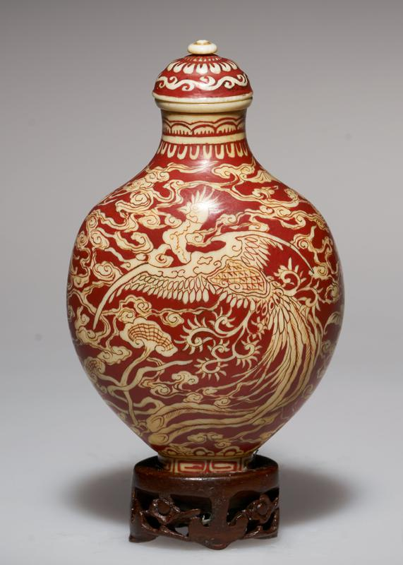 ivory, overlaid with red lacquer; ivory top; design shows the Phoenix and the Dragon in the Clouds; the three-clawed Dragon is, in China, the one commonly used for decoration; this is the Imperial Dragon of Japan; the Peach near the Dragon is the Symbol of marriage; the Phoenix, or Ho Ho Bird descends to earth to ring good tidings; he Bat is a Symbol of happiness