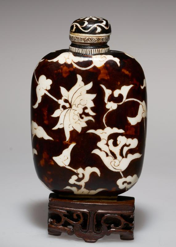 snuff bottle of ivory, overlaid with black lacquer; ivory top; design etched in geometric flower design