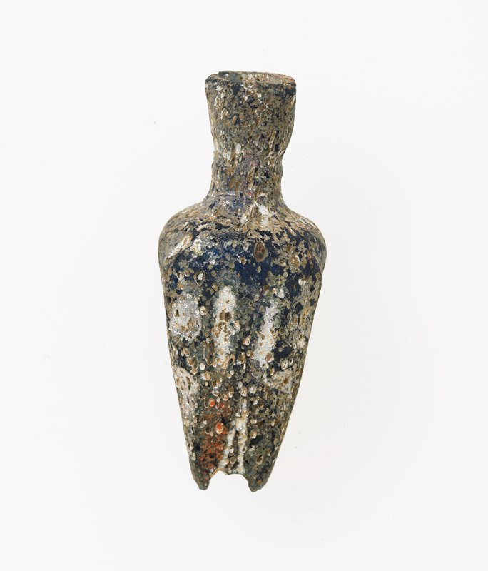 Vase, glass, deep clear blue bottle with crude diamond forms at corners continued into short legs, small cylindrical neck enlarges to hexagonal deep rim, color hidden largely by irridescence, Egyptian, century? cat. card dims H. 2'. Cosmetic vessel; deep blue irridescent cut glass
